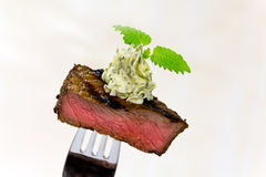 Gourmet Time,piece of a grilled steak with herb. Piece of a grilled steak with herb butter on a fork Stock Photos