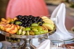 Gourmet- uppsättning för buffétabell med frukt och sötsaker Druvor äpplen, Fotografering för Bildbyråer