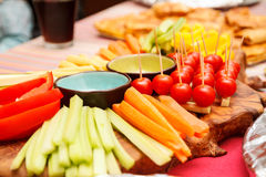 Gourmet Vegetable Platter on Party Buffet Table. Close Up Still Life of Chopped and Sliced Vegetables Arranged Neatly on Wooden Platter with Various Dips and Royalty Free Stock Photography