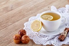 Gourmet tea cup with lemon, cinnamon sticks and tasty muffins on a knitted napkin. Gourmet white porcelain tea cup with lemon, cinnamon sticks and tasty muffins Stock Photo