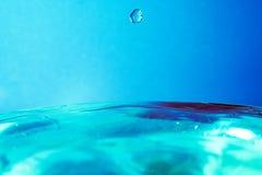 Goutte de l'eau tombant à l'eau bleue et à l'arrière-plan bleu Images stock
