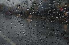Goutte de pluie et écoulement sur le verre Images stock