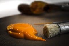 Goutte orange de peinture et deux pinceaux Photo libre de droits