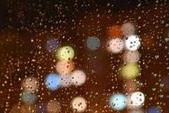 Gouttelettes de pluie de nuit sur l'hublot Photographie stock libre de droits