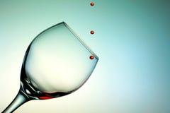 Gouttelettes de vin rouge tombant dans une tasse en verre Image libre de droits