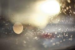 Gouttes de l'eau sur la surface du verre pendant le coucher du soleil Dans la photo il y a d'éclat des objets, la photo est hors  Photographie stock libre de droits