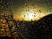 Gouttes de l'eau sur le verre de voiture conduisant sur la route sous la pluie photos stock