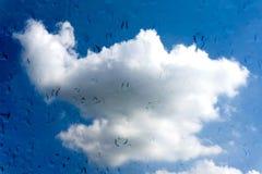 Gouttes de l'eau sur le vitrail au-dessus du ciel bleu Photographie stock libre de droits