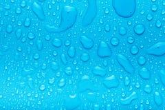Gouttes de l'eau sur un fond de couleur bleu Profondeur de fie Image stock