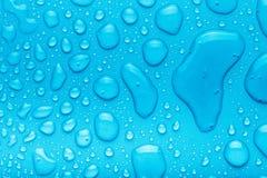 Gouttes de l'eau sur un fond de couleur bleu Profondeur de fie Photos libres de droits
