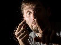Gouttes de l'eau sur un verre, visage de main et de mâle homme adulte se tenant à la fenêtre dans le jour pluvieux Photos libres de droits
