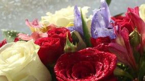 Gouttes de l'eau tombant sur le beau bouquet des roses, de l'iris et de l'alstroemeria banque de vidéos