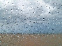 Gouttes de pluie sur la fenêtre avec le fond de plage Image libre de droits