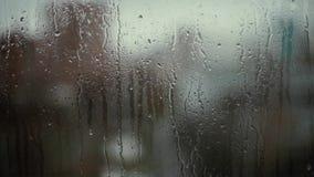 Gouttes de pluie sur le bokeh en verre de fond banque de vidéos