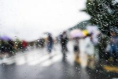 Gouttes de pluie sur le fond en verre bleu Lumières de Bokeh de rue hors focale Parapluies colorés Autumn Abstract Backdrop image libre de droits
