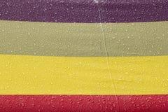 Gouttes de pluie sur un parapluie coloré images stock