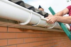 Gouttière de toit d'installation et de réparation d'entrepreneur de Roofer Réparation de gouttières avec des mains photos stock