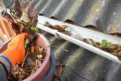 Gouttières de pluie nettoyant des feuilles Nettoyage de gouttière de toit d'amiante Photos stock