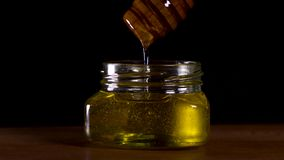 ?goutture de miel de plongeur de miel  sur le fond noir Miel épais organique sain plongeant de la cuillère en bois de miel banque de vidéos