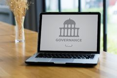 GOVERNANCE and building, Authority Computing Computer Laptop wit. H screen on table Silhouette and filter sun Royalty Free Stock Photo