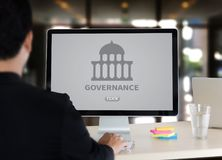 GOVERNANCE and building, Authority Computing Computer Laptop wit. H screen on table Silhouette and filter sun Royalty Free Stock Image