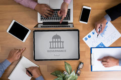 GOVERNANCE and Government building, Authority Government. Business team hands at work with financial reports and a laptop, top view Royalty Free Stock Photo