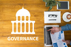 GOVERNANCE and Government building, Authority Government. Businessman working at office desk and using computer and objects, coffee, top view Royalty Free Stock Photos