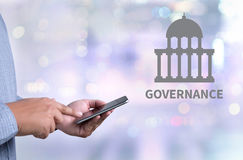 GOVERNANCE and Government building, Authority Government. Person holding a smartphone on blurred cityscape background Royalty Free Stock Photos