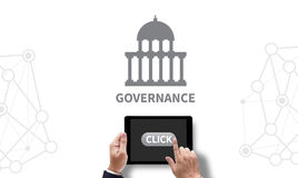GOVERNANCE and Government building, Authority Government. On the tablet pc screen held by businessman hands - online, top view Stock Image
