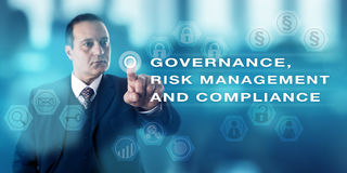 GOVERNANCE, RISK MANAGEMENT AND COMPLIANCE. Mature business man with focused gaze is pushing a virtual button to activate GOVERNANCE, RISK MANAGEMENT AND Stock Photos