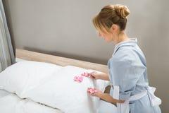 Governante che decora i cuscini con i petali Fotografia Stock