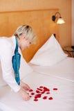 Governante che decora letto con i petali fotografie stock libere da diritti