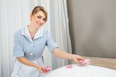 Governante che decora letto con i petali Immagine Stock