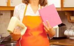 Governante con il libro di cucina ed il miscelatore immagini stock libere da diritti