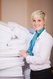 Governante femminile che impila gli strati nella stanza di riserva fotografia stock