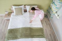 Governante femminile che sistema lenzuolo sul letto immagine stock libera da diritti