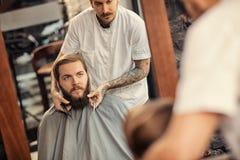 Governare dell'uomo del barbiere dei pantaloni a vita bassa reali fotografie stock