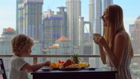 Governess молодой женщины имеет завтрак с мальчиком на балконе обозревая небоскребы центра города сток-видео