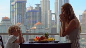 Governess молодой женщины имеет завтрак с мальчиком на балконе обозревая небоскребы центра города акции видеоматериалы