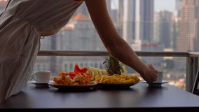 Governess молодой женщины подготавливая завтрак на балконе обозревая небоскребы центра города акции видеоматериалы