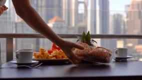 Governess молодой женщины подготавливая завтрак на балконе обозревая небоскребы центра города сток-видео