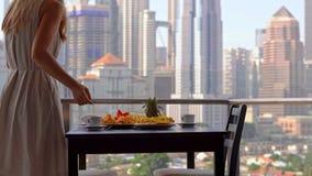 Governess молодой женщины подготавливая завтрак на балконе обозревая небоскребы центра города видеоматериал