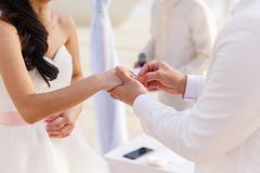 Governi dare un anello di fidanzamento alla sua sposa sotto il deco dell'arco fotografia stock libera da diritti