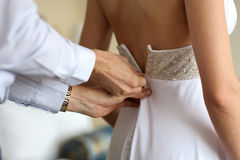 Governi il birde d'aiuto per mettere il vestito da cerimonia nuziale sopra Immagine Stock