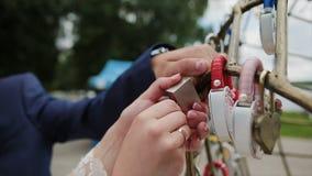 Governi il lucchetto d'attaccatura di nozze sul tubo vicino a vari lucchetti Serrature variopinte di nozze che appendono sui tubi stock footage