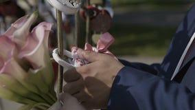 Governi il lucchetto d'attaccatura di nozze sul tubo vicino a vari lucchetti Serrature variopinte di nozze che appendono sui tubi archivi video