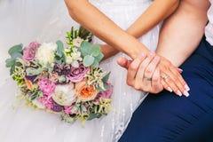 Governi l'abbraccio la sposa con il bello mazzo di nozze fotografia stock