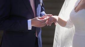 Governi la fede nuziale d'uso sulla mano del ` s della sposa stock footage