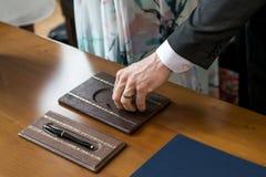 Governi la mano maschio che prende la fede nuziale dalla sposa della scatola durante la cerimonia Fotografia Stock