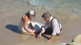 Governi la sposa della tenuta nelle sue armi dal mare stock footage